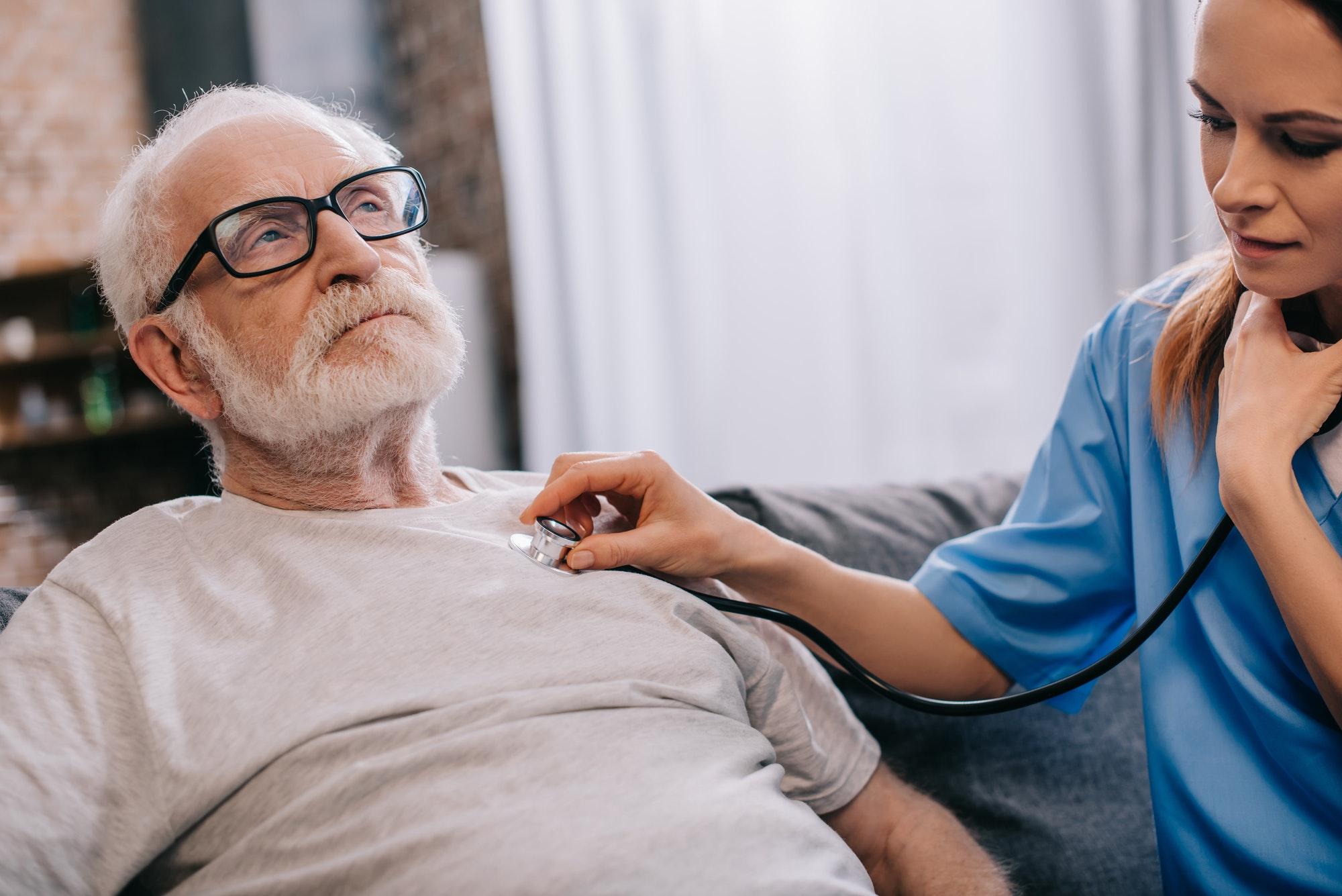 Nurse with stethoscope checking heartbeat of senior man